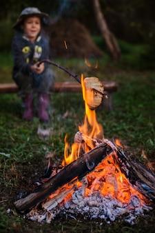 Um menino em um piquenique sentado perto do fogo e frite o pão no palito. fogueira no acampamento ao ar livre.