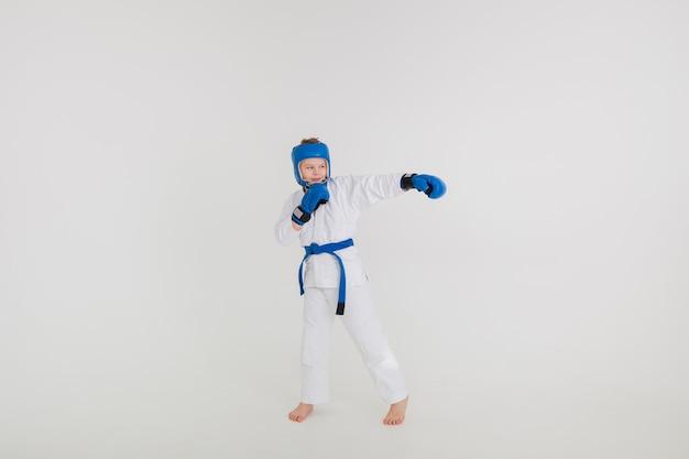 Um menino em um quimono branco e usando um capacete e luvas esportivas em uma parede branca