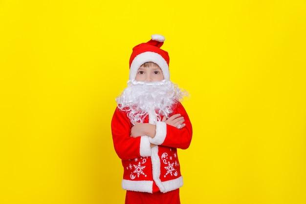 Um menino em um terno ad santaclaus e uma barba artificial cruza os braços sobre o peito