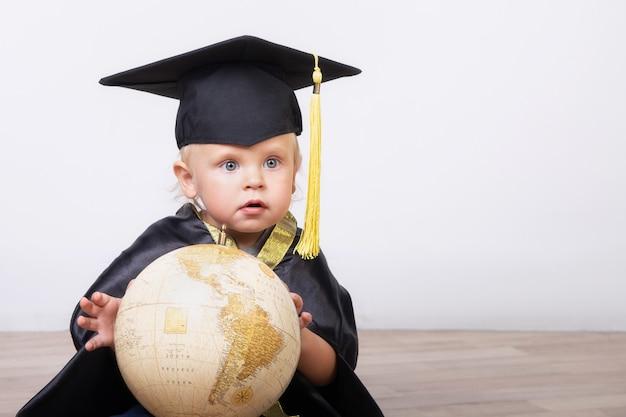 Um menino em um terno de solteiro ou mestre com um globo