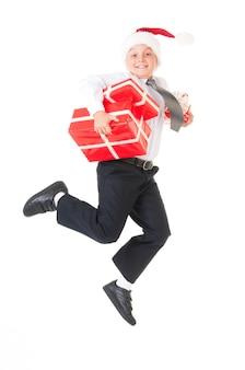 Um menino em uma camisa branca e um chapéu de ano novo papai noel está pulando com presentes vermelhos