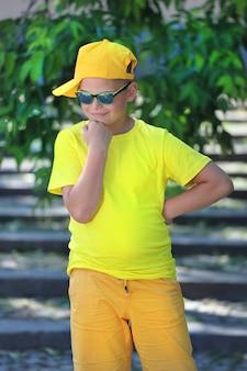 Um menino em uma camiseta amarela, boné e óculos escuros está na natureza. foto de alta qualidade