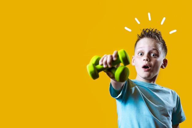 Um menino em uma camiseta brilhante com halteres em um fundo amarelo