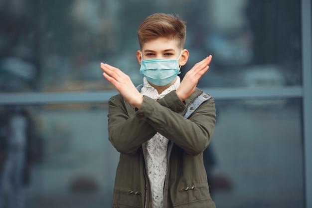 Um menino em uma máscara descartável, cruzando os braços
