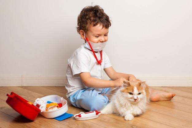Um menino em uma máscara médica com um estetoscópio brinca com um gato descontente no hospital.