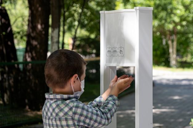 Um menino em uma máscara protetora lava bem as mãos com um desinfetante para proteger contra micróbios em um local público