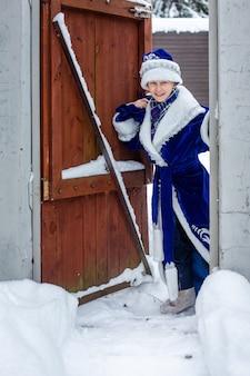 Um menino em uma roupa de papai noel com um saco de presentes entra em um portão de madeira.