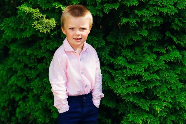 Um menino em uma roupa festiva mantém as mãos nos bolsos no fundo de uma árvore verde e olha seriamente para a lente da câmera