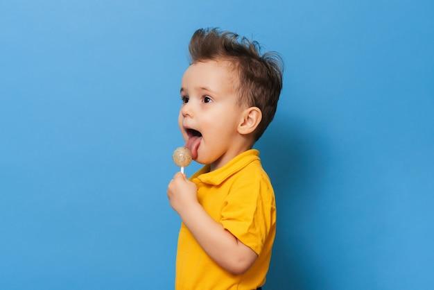 Um menino encantador segurando um pirulito. prevenção de cárie infantil