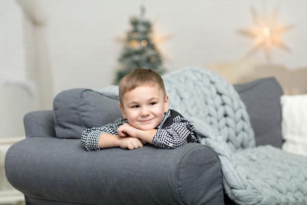 Um menino encontra-se em um sofá coberto com um cobertor de malha cinza e sorri