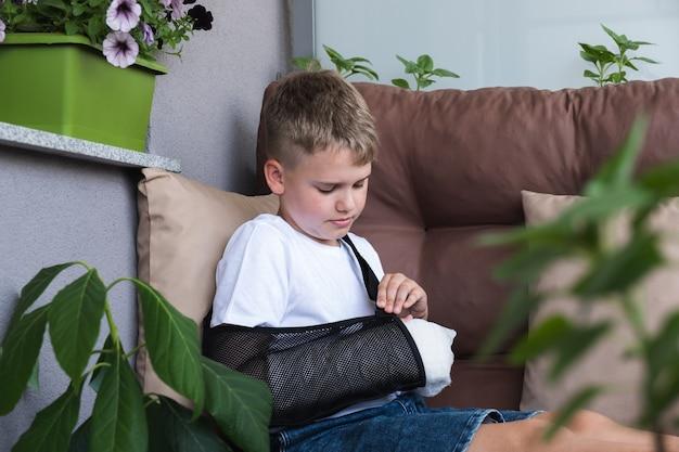 Um menino endireita uma tipoia em um braço quebrado