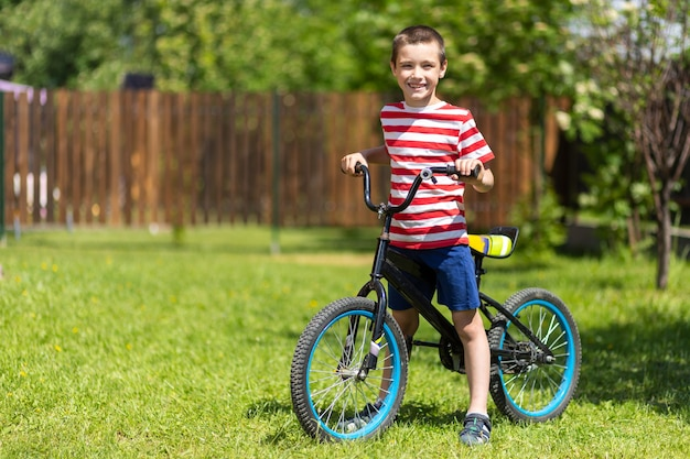 Um menino engraçado andando de bicicleta ou de bicicleta no verão