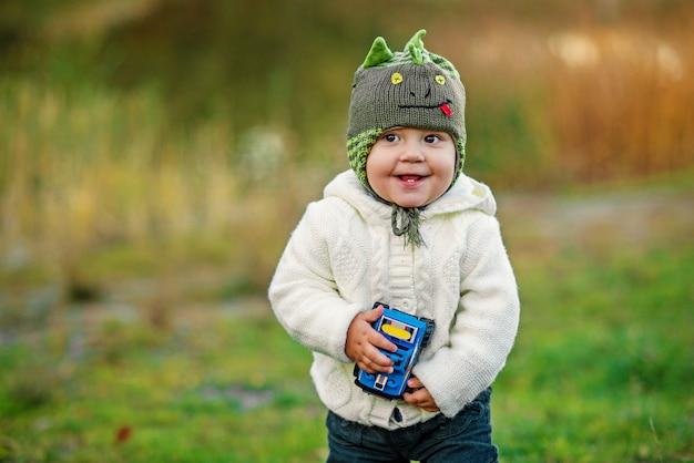 Um menino engraçado com dois dentes em roupas quentes, brincando com o carro de brinquedo na grama verde na sunset.