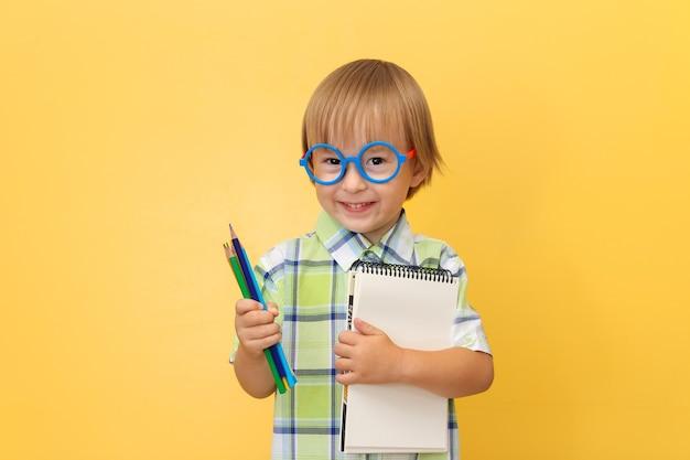 Um menino engraçado e alegre de camiseta e óculos, segurando um bloco de notas e lápis