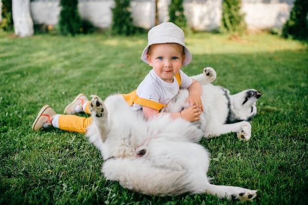 Um menino engraçado posando com o cachorro no jardim