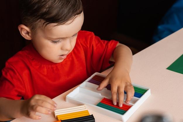 Um menino esculpe figuras de plasticina multicolorida sentado a uma mesa. educação pré-escolar. passatempo. auto desenvolvimento