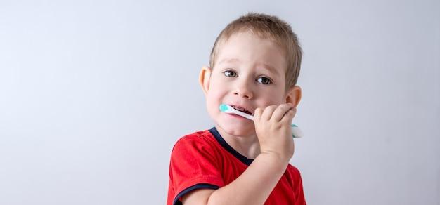 Um menino está aprendendo a escovar os dentes com uma escova de dentes