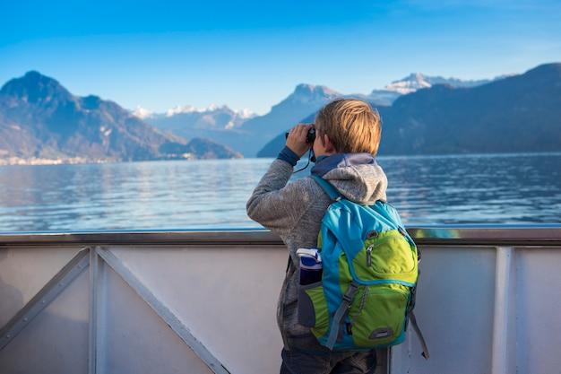 Um menino está assistindo a paisagem de binóculos