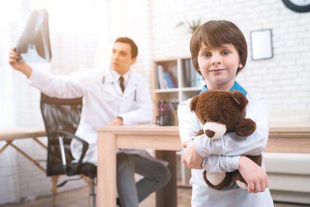 Um menino está de pé com um ursinho de pelúcia na sala médica.