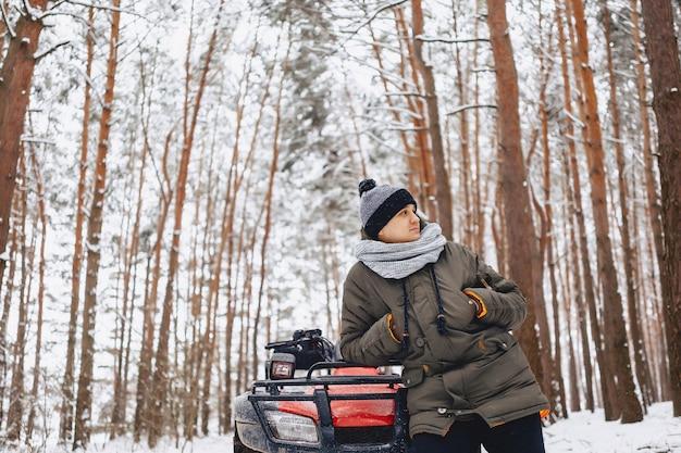 Um menino está de pé perto de uma moto no meio da floresta