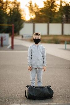 Um menino está em um campo de esportes após um treino ao ar livre durante o pôr do sol usando uma máscara
