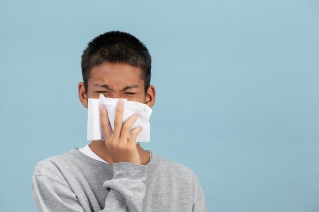 Um menino está espirrando nos tecidos e se sentindo doente na parede azul.