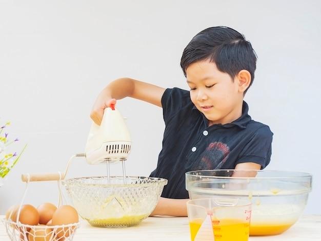 Um menino está fazendo bolo