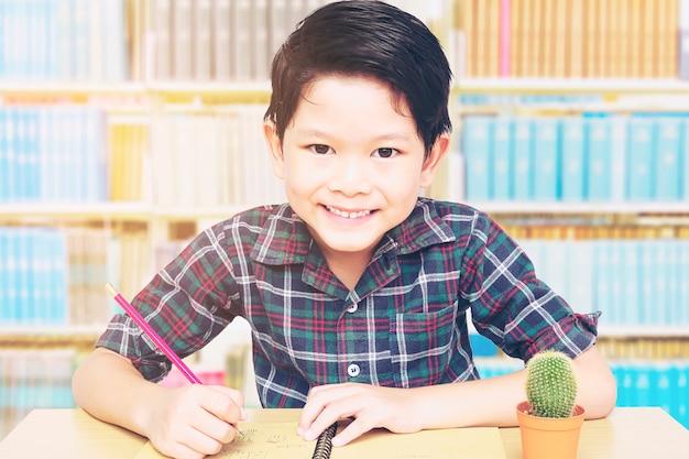 Um menino está feliz fazendo lição de casa em uma biblioteca