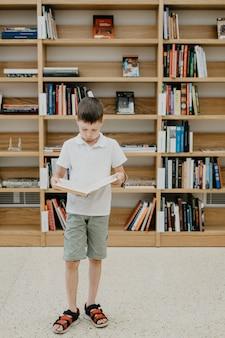 Um menino está na biblioteca e lê um livro em pé preparando-se para o dever de casa