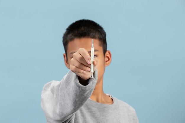 Um menino está segurando o termômetro com camisa cinza de manga comprida na parede azul.
