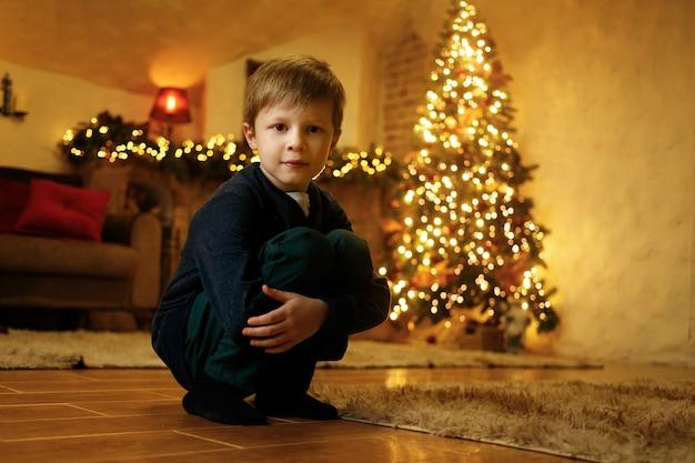 Um menino está sentado no chão em uma sala festiva na véspera do ano novo