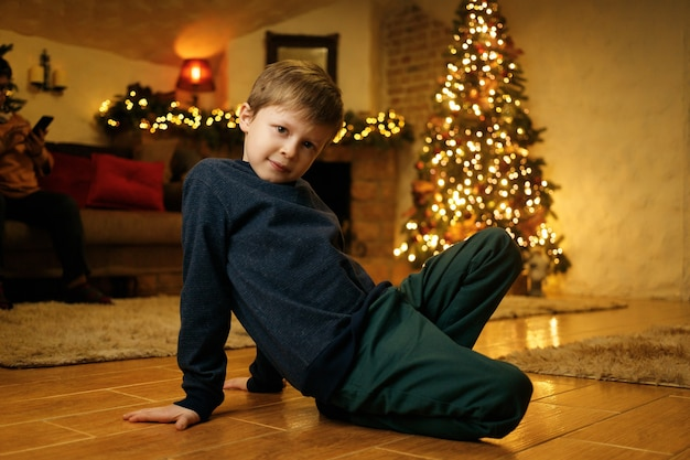 Um menino está sentado no chão em uma sala festiva na véspera do feriado de natal