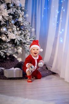 Um menino fantasiado de papai noel em um quarto decorado de natal perto da árvore de natal em um fundo de luzes.