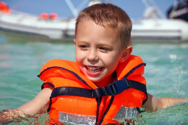 Um menino feliz com um colete salva-vidas no mar