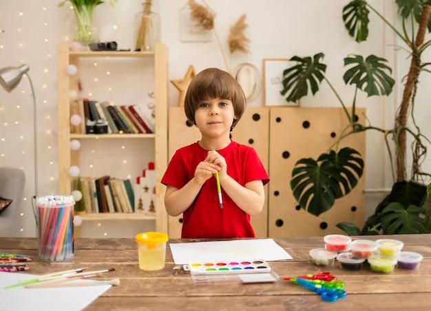 Um menino feliz com uma camiseta vermelha desenha com um pincel e pinta em papel branco em uma mesa de madeira