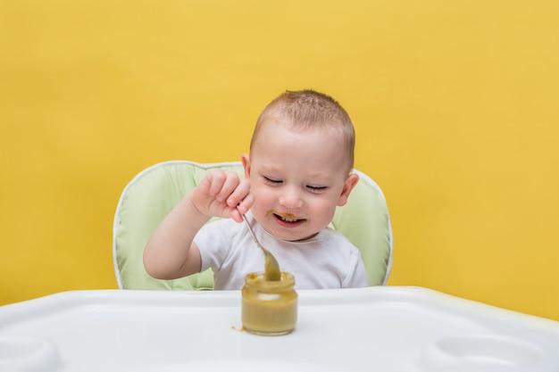 Um menino feliz come comida de bebê por conta própria em uma mesa em um amarelo isolado
