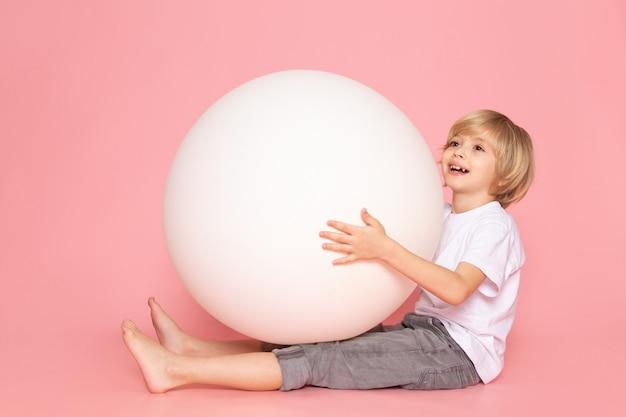 Um menino feliz loira vista frontal em camiseta branca, jogando com bola branca na mesa-de-rosa