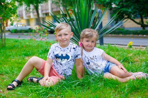 Um menino feliz novo e sua irmã bonito pequena que andam em um dia de verão morno.