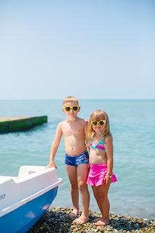 Um menino feliz novo e sua irmã bonito pequena que andam na costa de mar em um dia de verão morno.