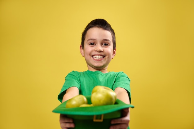 Um menino feliz segura um chapéu de duende cheio de maçãs na frente dele para a câmera