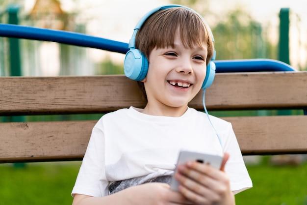 Um menino feliz sentado na rua em um banco com fones de ouvido, um telefone e um sorriso