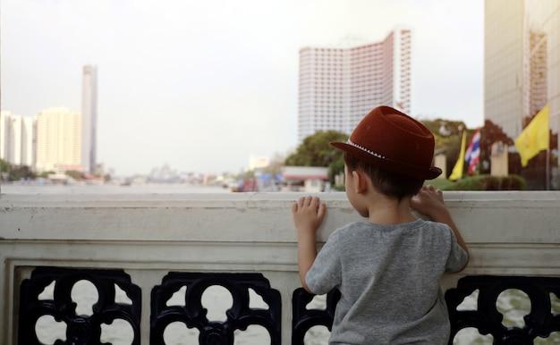 Um menino fica de costas no rio.