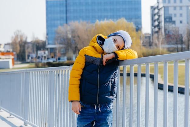 Um menino fica de máscara cinza durante uma quarentena com espaço livre. quarentena na máscara.