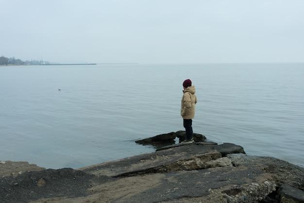 Um menino fica em uma pedra no mar negro e olha para a água