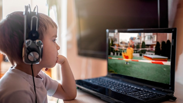 Um menino fofo assistindo as notícias da moda sobre lugares públicos fechados pela vida na internet em tempo de quarentena