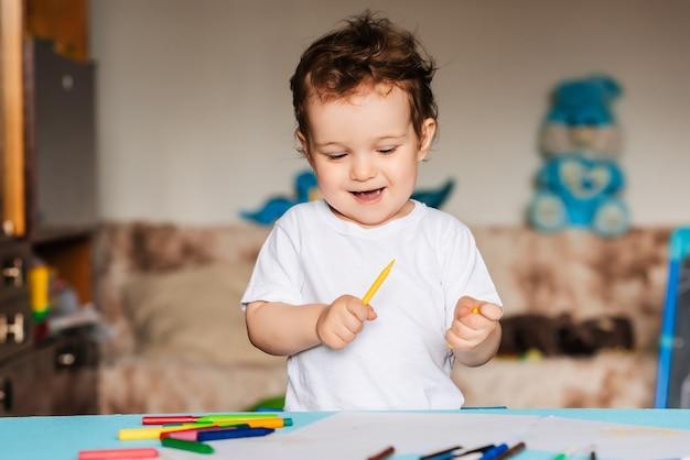 Um menino fofo desenha em seu caderno de desenhos com lápis de cor
