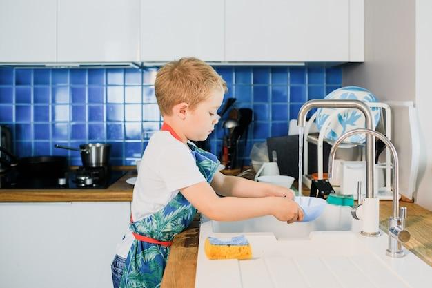 Um menino lava pratos em uma cozinha moderna