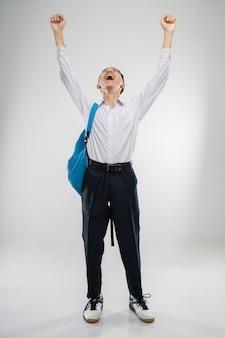 Um menino levanta a mão em um uniforme do ensino fundamental em alto astral com uma mochila escolar