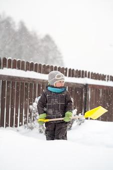 Um menino limpa caminhos de uma pá no quintal de neve