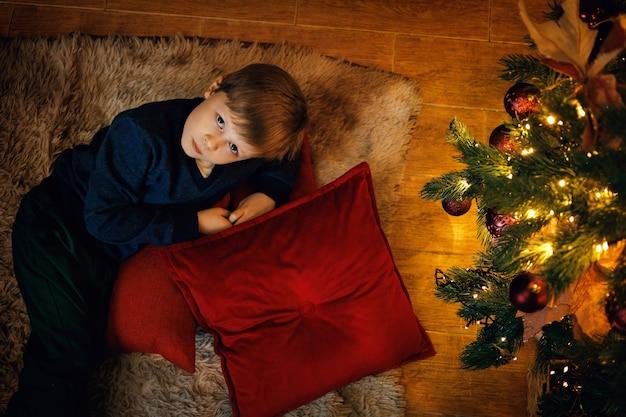Um menino loiro de 57 anos está deitado no tapete perto da árvore de ano novo olhando para a câmera